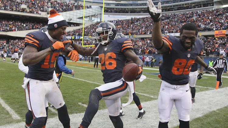 FILE - In this Oct. 28, 2012, file photo, Chicago Bears cornerback Tim Jennings (26) celebrates with teammates Brandon Marshall (15) and Earl Bennett (80) after he returned and interception for a touchdown during the second half of an NFL football game against the Carolina Panthers in Chicago.   The Bears has seven interception returns for touchdowns and eight scores on defense this season. (AP Photo/Nam Y. Huh, File)