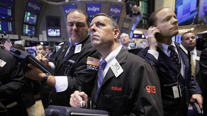 Traders Anthony Riccio, Edward Baumann, and Andrew Igoe, left to right, work on the floor of the New York Stock Exchange Tuesday, Aug. 16, 2011. (AP Photo/Richard Drew)