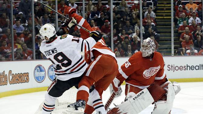 Detroit Red Wings defenseman Niklas Kronwall, center, of Sweden, checks Chicago Blackhawks center Jonathan Toews (19) away from goalie Jimmy Howard (35) during the first period in Game 4 of the Western Conference semifinals in the NHL hockey Stanley Cup playoffs in Detroit, Thursday, May 23, 2013. (AP Photo/Paul Sancya)