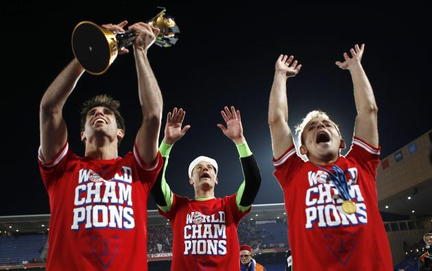 Javier Martinez of Germany's Bayern Munich holds the trophy as he celebrates with goalkeeper Manuel Neuer and Rafinha after winning their 2013 FIFA Club World Cup final soccer match against Morocc