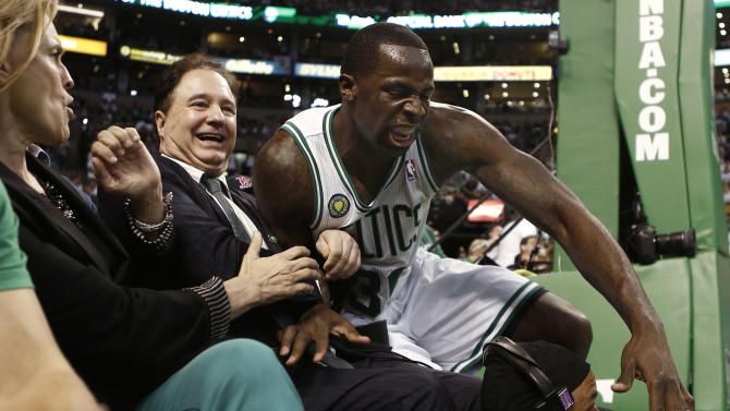 Boston Celtics' Brandon Bass lands in the lap of Boston Celtics co-owner Stephen Pagliuca during the second quarter of Game 3 of a first round NBA basketball playoff series against the New York Knicks, Friday, April 26, 2013, in Boston. (AP Photo/Winslow Townson)