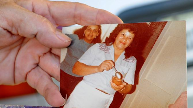 Miladys Ortega shows a photograph of her sister, Yoselyn Ortega, front center, taken some time between 1985 and 1990, at her home in Santiago, Dominican Republic, Saturday, Oct. 27, 2012. Yoselyn Ortega, a 50-year-old naturalized U.S. citizen, is accused of stabbing to death two children in her care at a New York Upper West Side apartment on Thursday, Oct. 25, 2012. Yoselyn Ortega was in critical condition Friday with what police said were self-inflicted knife wounds, and investigators were unable to question her, in part because she was still breathing with the help of a tube. (AP Photo/Manuel Morel)