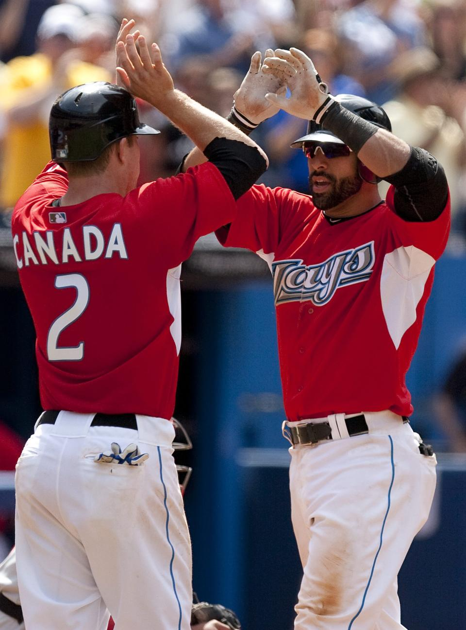 Toronto Blue Jays' Jose Bautista, right, celebrates hitting a two-run home run against Philadelphia Phillies with teammate Aaron Hill during the seventh inning of an interleague baseball game in Toronto on Friday, June 1, 2011. (AP Photo/The Canadian Press, Chris Young)