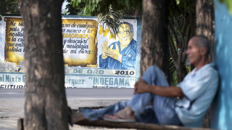 A man rests across the street from a mural of Nobel laureate Gabriel Garcia Marquez in Aracataca, the city were he was born in Colombia's Caribbean coast, Friday, April 18, 2014. Garcia Marquez died in Mexico City on April 17, 2014. (AP Photo/Ricardo Mazalan)