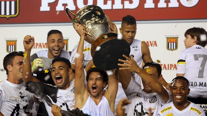 Santos soccer players raise the Sao Paulo state championship trophy after their final soccer match against Palmeiras in Santos