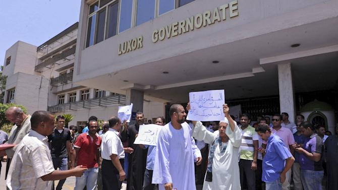"Tourism workers and activists in Luxor  protest a newly appointed Islamist governor and block his office Tuesday June 18, 2013. Adel el-Khayat was named to the provincial governor's post Sunday by President Mohammed Morsi, causing outrage because of his links to Gamaa Islamiya, which waged an armed insurgency against the state starting in 1992 and attacked police, Coptic Christians and tourists. Tourism is the lifeblood of Luxor but it has been hit hard by the downturn in foreign visitors since the Arab Spring unleashed political turmoil since 2011. Signs in Arabic read, ""The plot you are hatching, we will undo"" and  ""leave terrorist."" (AP Photo/Ibrahim Zayed)"