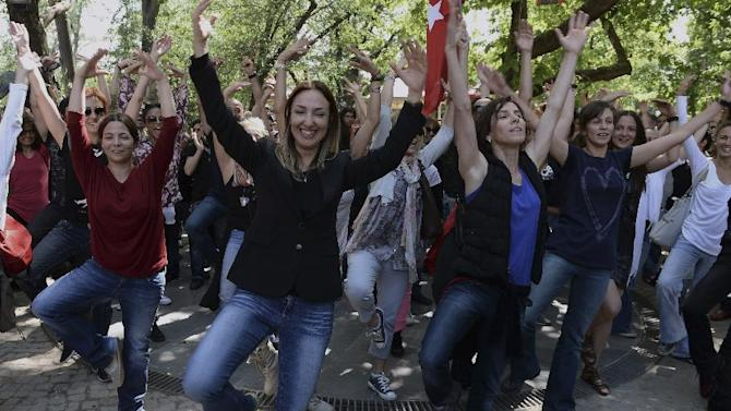 People dance in the city's Kugulu Park, where a group continue reading books, dancing or playing musical instruments in Ankara, Turkey, Friday, June 7, 2013. A senior European Union official, the EU enlargement commissioner Stefan Fule on Friday criticized Turkish police's harsh crackdown on protesters in the last week, asked that abusers be investigated and punished and told an audience that included Turkish prime minister Recep Tayyip Erdogan, that as a EU-candidate country, Turkey should aspire to the highest standards of democracy.(AP Photo)