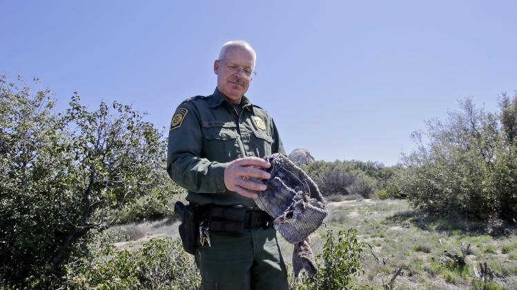 """In this Monday, March 25, 2013 photo, Border Patrol agent Richard Gordon, a 23-year veteran of the agency, holds a foot wrap made of carpet and wire which illegal immigrants use to disguise their footprints while trying to avoid being tracked after entering the United States in the Boulevard area east of San Diego in Boulevard, Calif. For the past 16 years Gordon has been one of the top """"sign-cutters"""" or trackers in the Border Patrol. (AP Photo/Lenny Ignelzi)"""