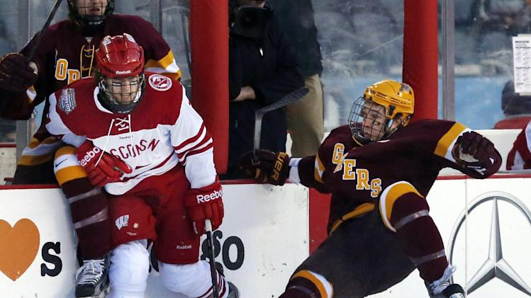 Wisconsin forward Tyler Barnes, left, side-steps a check attempt by Minnesota defenseman Jake Parenteau during the first period of a college hockey game at Chicago's Soldier Field, Sunday, Feb. 17, 2013. (AP Photo/Charles Rex Arbogast)