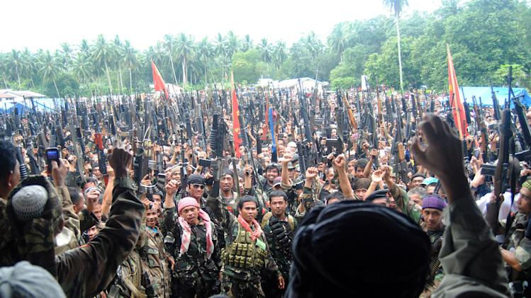 FILE - In this Jan. 3, 2013 file photo, thousands of Moro National Liberation Front (MNLF) members, who signed a peace agreement with the Philippine government in 1996, display their weapons during a rally on the volatile island of Jolo in southern Philippines. After years of fighting the government from hidden jungle bases in the southern Philippines, an Al-Qaida-linked militant group is facing a new adversary: fellow Muslim insurgents who can match their guerrilla battle tactics and are eager to regain their lost stature by fighting the widely-condemned terrorist group. The emerging enmity between the Abu Sayyaf militants and the Moro rebels could bolster a decade-long campaign by the Philippines and Western countries to isolate the al-Qaida offshoot Abu Sayyaf, which remains one of the most dangerous groups in Southeast Asia.(AP Photo/Nickee Butlangan, File)
