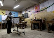 An Egyptian woman casts her vote a few minutes before the closure of polling stations in Cairo. Egypt&#39;s ruling military council on Sunday issued an amended constitutional document handing it sweeping powers, including legislative control, after a court ruled the elected parliament invalid