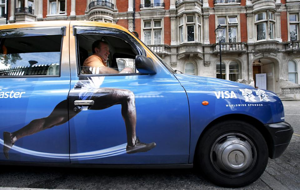 In this Wednesday, Aug. 8, 2012 photo, taxi driver Richard Meid waits for a fare in front of the British Museum during the 2012 Summer Olympics, in London. (AP Photo/Jae C. Hong)