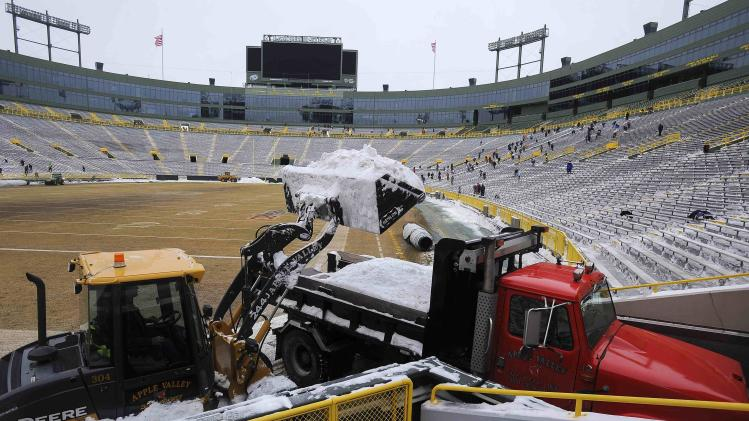 A tractor dumps snow into the back of a truck after it was cleared from the bleachers by paid volunteers at Lambeau Field in Green Bay