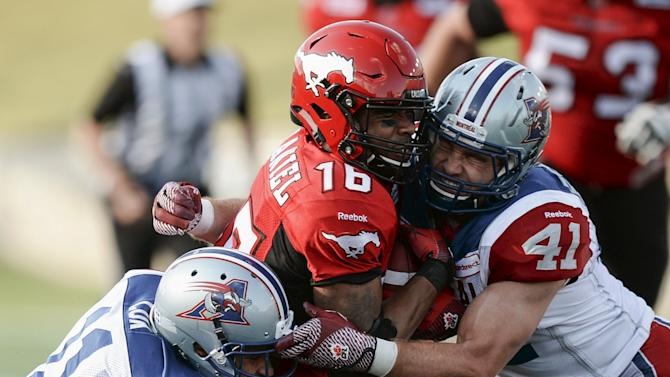 Calgary Stampeders' McDaniel is sandwiched by Montreal Alouettes' Cox and Elsworth during their CFL football game in Calgary