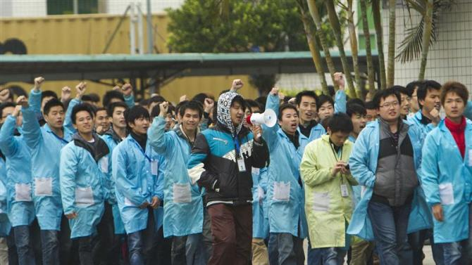 IBM workers shout slogans as they protest at an IBM factory in Shenzhen