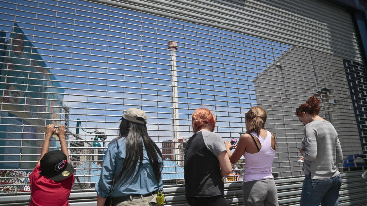 Visitors stand outside a locked entry to Coney Island amusement park in an area near the Astrotower, center, on Wednesday, July 3, 2013 in New York. The park remains closed while workers examine the condition of the 275-foot-tall observation Astrotower. The park was evacuated on Tuesday after the fire department received a call that the tower was swaying. (AP Photo/Bebeto Matthews)