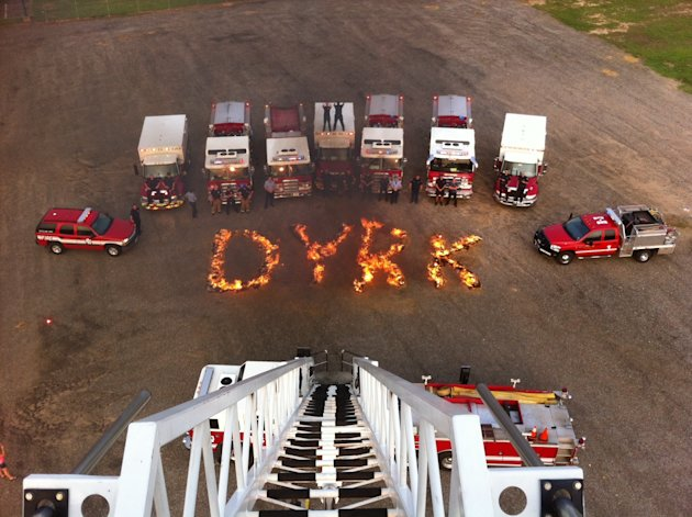 "In this June 10, 2012 photo, Longview, Texas firefighters pose in front of a design of burning hay spelling the name ""Dyrk"" in Longview, Texas. The firefighters are among several companies in Texas ho"