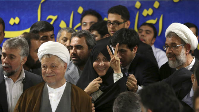 Former Iranian President Akbar Hashemi Rafsanjani, second left, is surrounded by supporters as his daughter, Fatemeh, center, flashes a victory sign as he registers his candidacy for the upcoming presidential election, at the election headquarters of the interior ministry in Tehran, Iran, Saturday, May 11, 2013. Iranian election authorities say several new high-profile politicians including hardliners, reformists, and allies of outgoing President Mahmoud Ahmadinejad have registered for the June 14 presidential elections. The campaign is taking shape as open season on Ahmadinejad's legacy and his combative style that bolstered his stature among supporters but alarmed critics. Ahmadinejad is barred by law from seeking a third term due to term limits under Iran's constitution. (AP Photo/Ebrahim Noroozi)