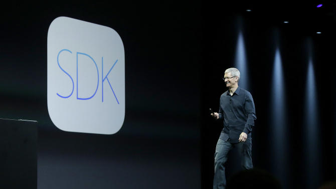 Apple CEO Tim Cook walks past a logo for SDK at the Apple Worldwide Developers Conference in San Francisco, Monday, June 2, 2014. (AP Photo/Jeff Chiu)