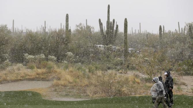Volunteers make their way off the course as snow and rain fall during the Match Play Championship golf tournament, Wednesday, Feb. 20, 2013, in Marana, Ariz. Play was suspended for the day. (AP Photo/Ted S. Warren)