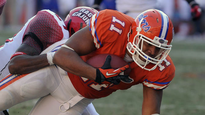 Florida tight end Jordan Reed (11) is hit by Louisiana-Lafayette safety T.J. Worthy (27) after catching a pass during the second half of an NCAA college football game in Gainesville, Fla., Nov. 10, 2012. Florida defeated Louisiana-Lafayette 27-20. (AP Photo/Phil Sandlin)