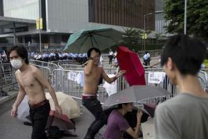 Protesters hold umbrellas in front of railings as police…