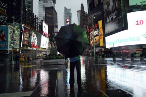 <p>A lone tourist stands in Times Square as New Yorkers prepare for Hurricane Sandy. The massive storm bashing the US East Coast froze commerce, shut down stock exchanges for the first time since the 9/11 attacks and idled millions of workers Monday, laying siege to an economy still trying to get out of first gear.</p>