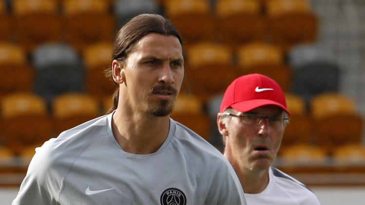 Paris Saint-Germain soccer player Ibrahimovic warms up with manager Blanc during a training session in Hong Kong