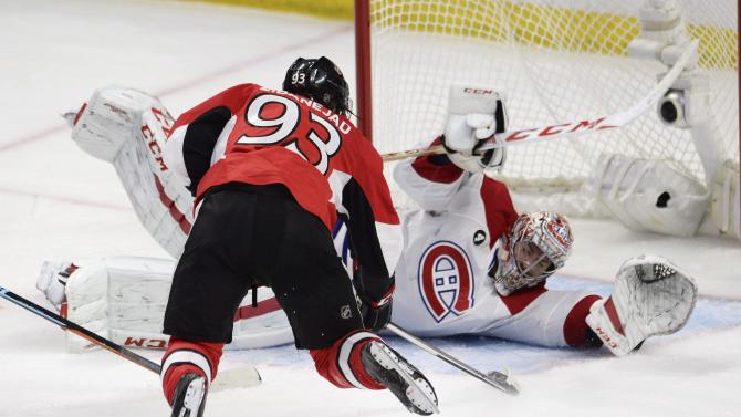 Montreal Canadiens goalie Carey Price sprawls in front of a leaping Ottawa Senators' Mika Zibanejad (93) during third period NHL playoff action in Ottawa, Ontario, Sunday, April 26, 2015. (Adrian Wyld/The Canadian Press via AP) MANDATORY CREDIT