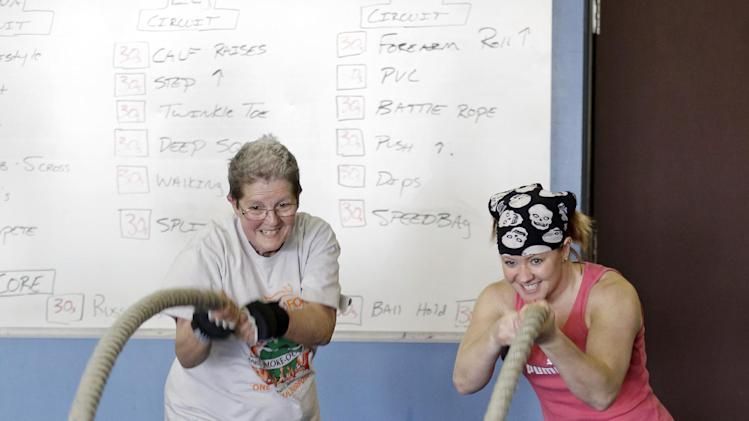 Mary Yeaman, left, and Instructor Kristy Rose Follmar use battle ropes to work out at Rock Steady Boxing in Indianapolis, Tuesday, April 9, 2013.  Rock Steady boxing offers a uniquely effective form of physical exercise to people who are living with Parkinson's. While focusing on overall fitness, workouts include: ring work, focus mitts, heavy bags, speed bags, jump rope, core work, calisthenics and circuit weight training. (AP Photo/Michael Conroy)