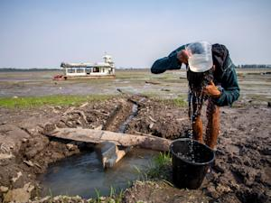 A man uses water from a pond on the dried-up bed of…