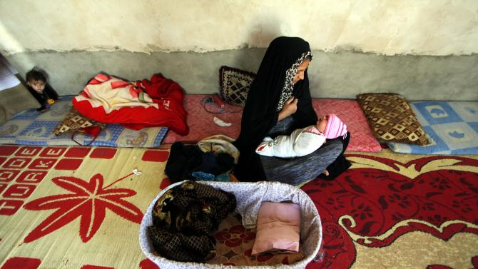 A displaced Iraqi woman, who fled from Islamic State violence in Mosul, sits inside a makeshift school tent in Najaf
