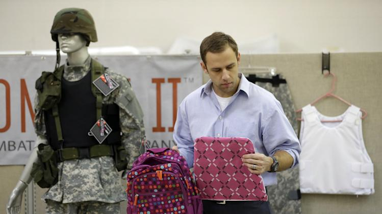 Rick Brand, Chief Operating Officer of Amendment II, holds a children's backpack, left, and anti-ballistic insert at the company's manufacturing facility in Salt Lake City, Wednesday, Dec. 19, 2012. Anxious parents reeling in the wake the Connecticut school shooting are fueling sales of armored backpacks for children emblazoned with Disney and Avengers logos, as firearms enthusiasts stock up on assault rifles nationwide amid fears of imminent gun control measures.  At Amendment II, sales of childrenís backpacks and armored inserts are up 300 percent. (AP Photo/Rick Bowmer)
