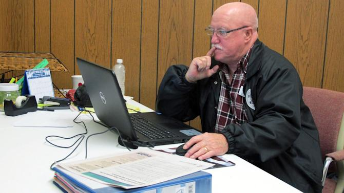 In this photo taken Tuesday, Dec. 17, 2013, Joe Manning sits in his office in De Funiak Springs, Fla. Manning is an outreach worker trained to sign people in rural Florida to participate in the Affordable Care Act. (AP Photo/Melissa Nelson)