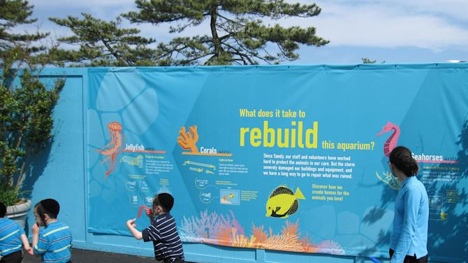In this May 31, 2013 photo, a sign outside of Coney Island's New York Aquarium details rebuilding efforts at the aquarium in the Brooklyn borough of New York. Eight months after Superstorm Sandy hit New York City, Coney Island's rides, eateries and beach are getting plenty of visitors, and there are even a few new attractions like a carousel and a store for fans of the Nets basektball team. (AP Photo/Beth Harpaz)