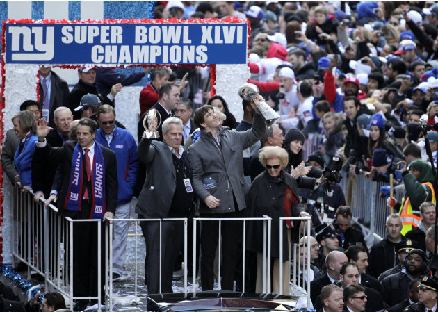 New York Giants' Eli Manning, second from right, holds up the Vince Lombardi trophy as a float makes its way up Broadway in New York, Tuesday, Feb. 7, 2012. Joining Manning are New York Gov. Andrew Cu