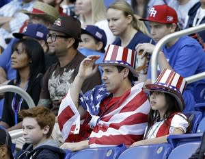 United States fans, foreground, look on during the first inning of the second round elimination game of the World Baseball Classic against Puerto Rico, Friday, March 15, 2013 in Miami. (AP Photo/Wilfredo Lee)