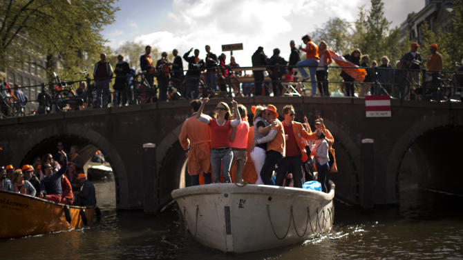 People dance on boats along a canal in Amsterdam as they celebrate the coronation of King Willem-Alexander Tuesday, April 30, 2013. At 46, Willem-Alexander is the youngest monarch in Europe and the first Dutch king in 123 years, since Willem III died in 1890. (AP Photo/Emilio Morenatti)