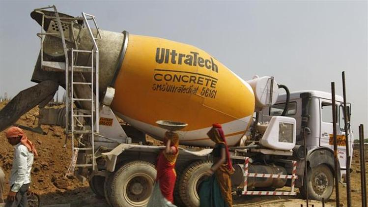 Workers walk in front of an UltraTech concrete mixture truck at the construction site of a commercial complex on the outskirts of Ahmedabad April 22, 2013. REUTERS/Amit Dave/Files