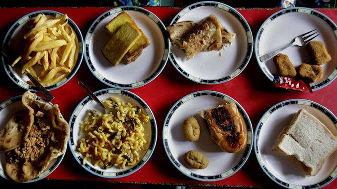 """Assorted lunch plates are arranged at a table for students at the Bahria Foundation school in Rawalpindi, Pakistan, Tuesday, May 6, 2014. Most of the kids seen there have home cooked food for lunch. Principal Syeda Arifa Mohsin says the school tries to dissuade parents from fixing junk food for their children. """"If we discover that a child has junk food, we ask his or her parents to please make a little effort for their child's health,"""" Mohsin says. (AP Photo/Anjum Naveed)"""