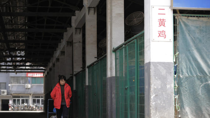 A worker pulls a cart though an empty live poultry wholesale market in Shanghai, China Wednesday, April 10, 2013. China said two more people have died of a new strain of bird flu, bringing the death toll to nine. Shanghai has suspended sales of live poultry. (AP Photo/Eugene Hoshiko)