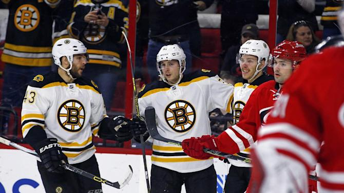 Boston Bruins' Ryan Spooner, second from left, celebrates his goal with teammates Matt Bartkowski (43) and David Pastrnak (88) during the first period of an NHL hockey game against the Carolina Hurricanes, Sunday, March 29, 2015, in Raleigh, N.C. Boston won 2-1 in overtime. (AP Photo/Karl B DeBlaker)