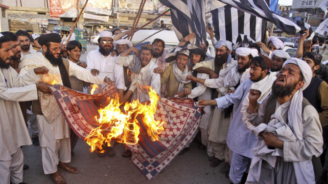 FILE - In this Friday, June 1, 2012 file photo, supporters of Pakistan Defense Council, a coalition of Islamic parties, burn a representation of a US flag at rally to condemn the reopening of the NATO supply line to neighboring Afghanistan, in Quetta, Pakistan. The U.S. and Pakistan are starting to look more like enemies than friends, threatening the U.S. fight against Taliban and al-Qaida militants based in the country and efforts to stabilize neighboring Afghanistan before American troops withdraw. The latest irritant is Pakistan's refusal to end its six-month blockade of NATO troop supplies meant for Afghanistan.(AP Photo/Arshad Butt)