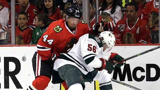 Minnesota Wild center Erik Haula, right, and Chicago Blackhawks defenseman Kimmo Timonen battle for the puck during the first period  of Game 2 in the second round of the NHL Stanley Cup hockey playoffs in Chicago, Sunday, May 3, 2015. (AP Photo/Nam Y. Huh)
