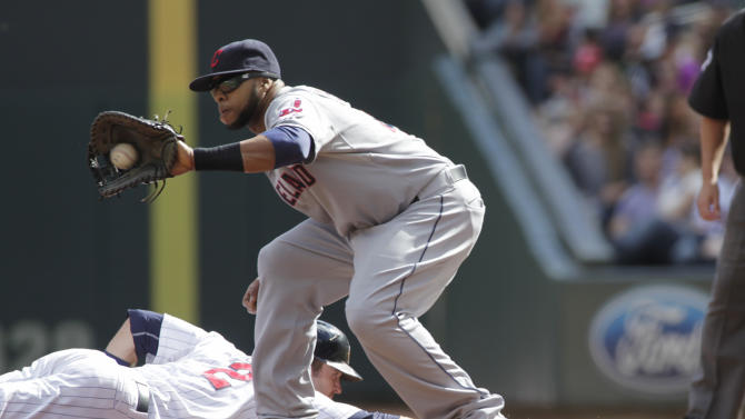 Minnesota Twins Brian Dozier, bottom, dives back to first as Cleveland Indians first baseman Carlos Santana takes the throw during the first inning of a baseball game Sunday, Sept. 21, 2014, in Minneapolis. AP Photo/Paul Battaglia)