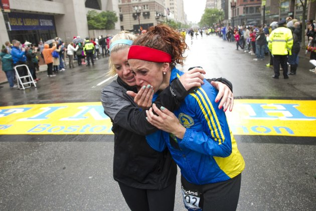 "Roy comforts Wulff as runners cross the finish line after completing the final mile of the Boston Marathon course during ""#onerun"" in Boston"