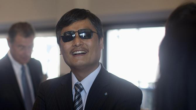 Chinese activist Chen Guangcheng talks with colleagues before speaking at the National Press Club in Washington, Wednesday, Oct. 2, 2013. Guangcheng says he has new affiliations with Lantos Foundation for Human Rights and Justice, the Catholic University of America and the William E. and Carol G. Simon Center on Religion and Constitution of the Witherspoon Institute after leaving New York University under disputed circumstances. (AP Photo/Carolyn Kaster)