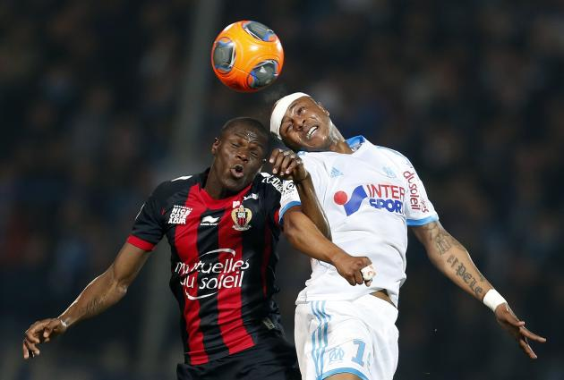 Olympique Marseille's Ayew jumps to head the ball with Nice's Genevois during their French Ligue 1 soccer match in Marseille
