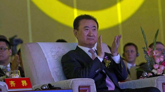 FILE - In this Wednesday, June 19, 2013, file photo, Wanda Chairman Wang Jianlin applauds in front of the logo for Dalian Wanda Group during an event at a hotel in Beijing, China. The Hurun Report, which follows China's wealthy, said Wednesday, Sept. 11, 2013, that Wang, whose Dalian Wanda Group Co. operates hotels, cinemas and department stores, was ranked No. 1 for the first time on Hurun's annual list of Chinese tycoons with a fortune of $22 billion. (AP Photo/Ng Han Guan, File)