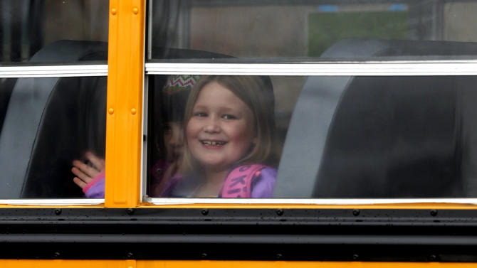 A young girl waves as her school bus pulls into Hawley School, Tuesday, Dec. 18, 2012, in Newtown, Conn.  Classes resumed Tuesday for Newtown, schools except those at Sandy Hook, following Friday's mass shooting at the Sandy Hook Elementary School. Buses ferrying students to schools were festooned with large green and white ribbons on the front grills, the colors of Sandy Hook. At Newtown High School, students in sweatshirts and jackets, many wearing headphones, betrayed mixed emotions. (AP Photo/Jason DeCrow)